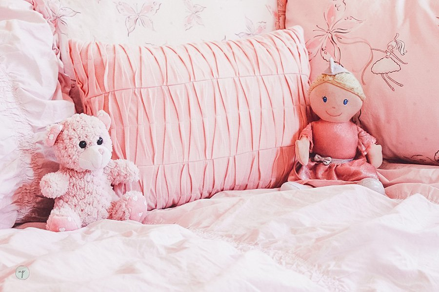 close up of princess doll and stuffed bear on bed