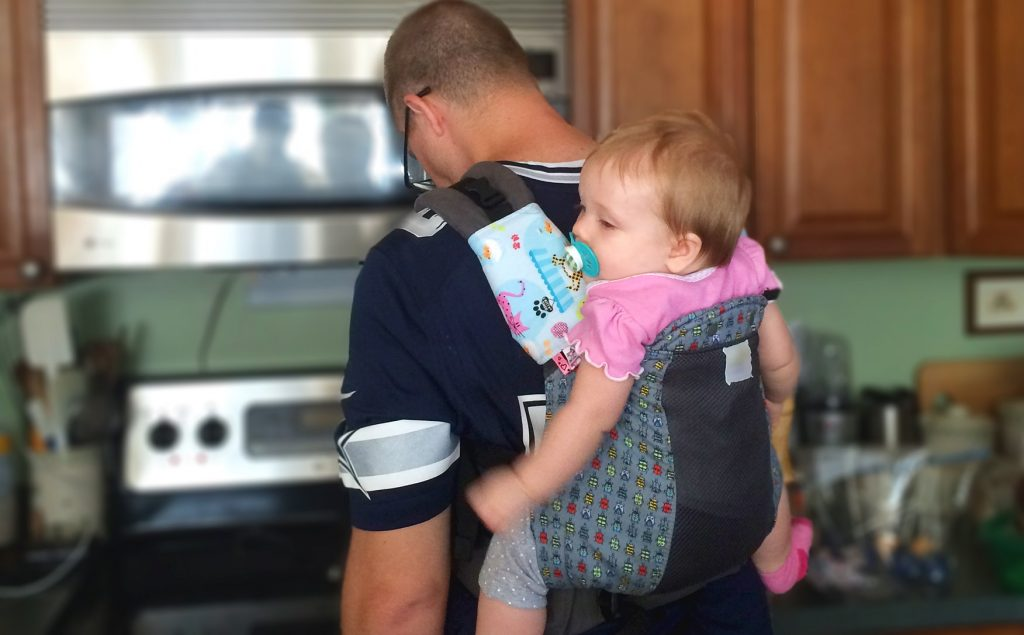 Dad faces stove, cooking, while wearing toddler in carrier on his back