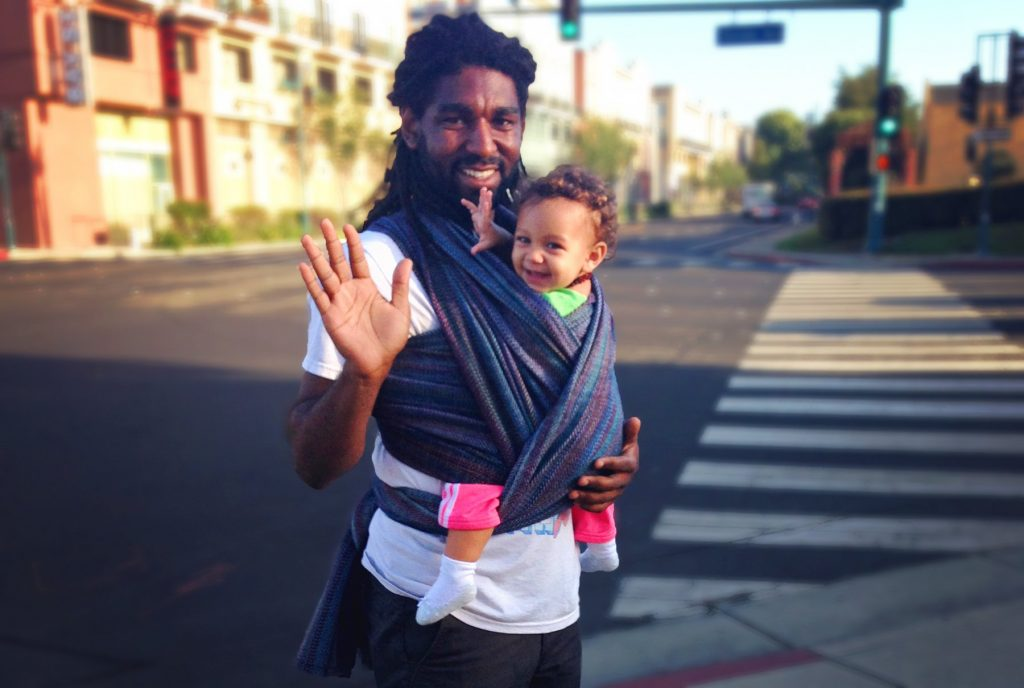 babywearing dad waves at camera