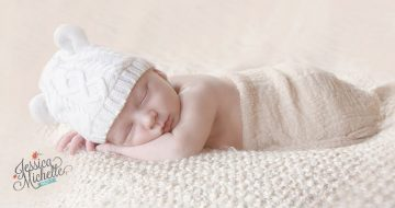 newborn sleeping on a blanket