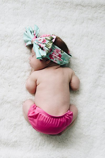 baby girl sleeping on her tummy with pink cloth diaper on