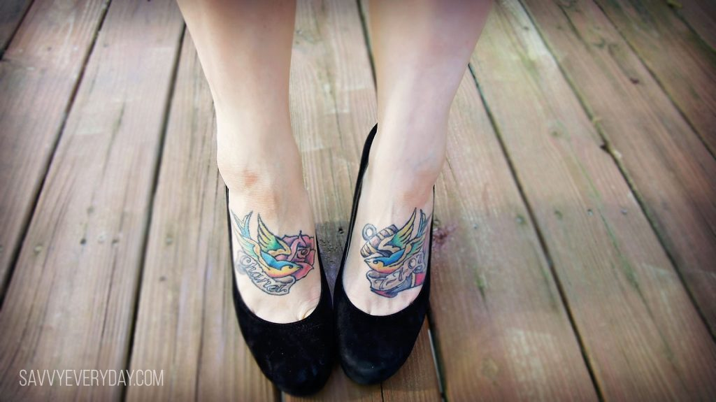 Close up of woman's feet (in heels), with tatoos on the tops of her feet.