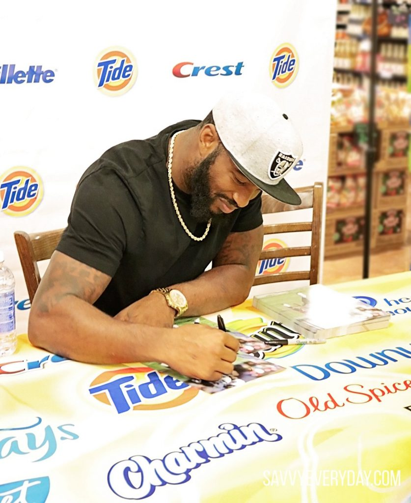 Marcel smiles while signing