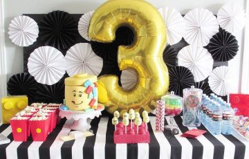 Image of a LEGO-themed 3rd Bday table with balloon, cake and snacks