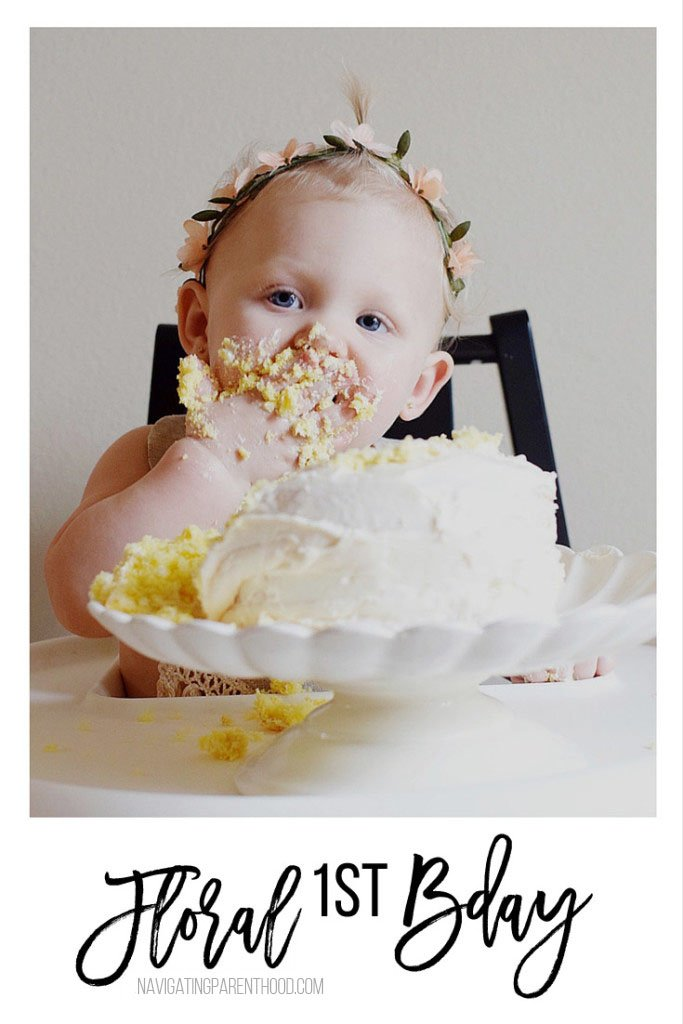 baby eating birthday cake in white highchair