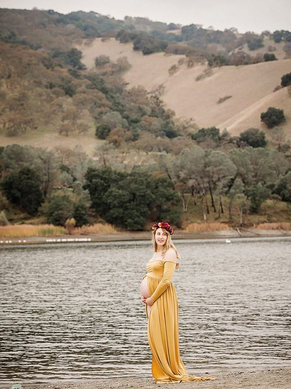 maternity photo of mom standing by water