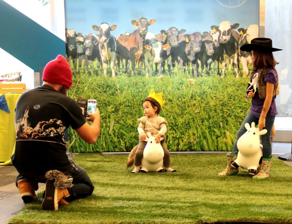 dad taking pics of kids in front of photo backdrop at MommyCon