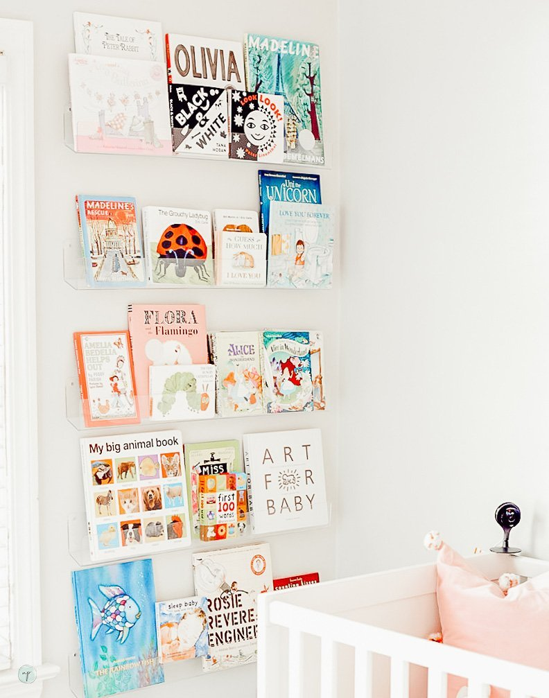 Beautiful clear bookshelf full of tot books in Wonderland nursery