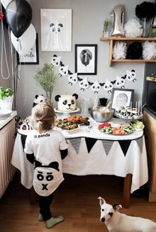 boy wearing panda t-shirt staring at panda-themed birthday treat table with a panda cake