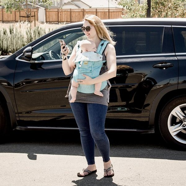 Mom standing outside with baby in baby carrier looking at YourMechanic app