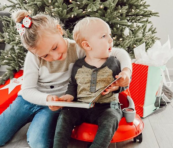 River and S reading a book by the Christmas tree