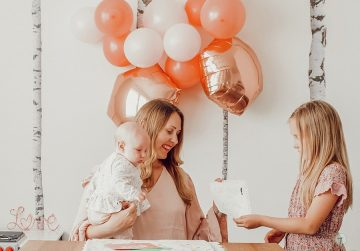 mom holding baby while older daughter hands her a drawing
