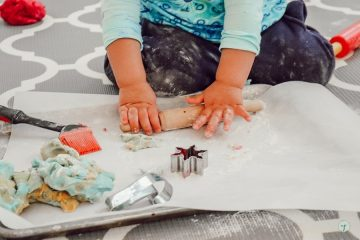 close up of toddler hands using rolling pin on playing dough in a sheet pan