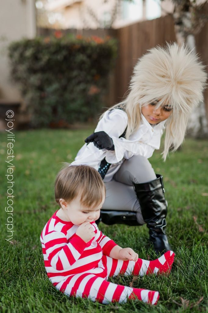 Little girl dressed as Labyrinth king character bends down to reach baby brother