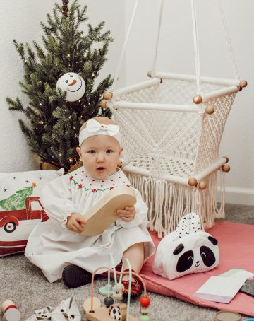 baby in Christmas clothes sitting on floor with toys