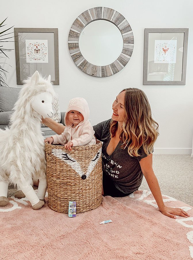 baby stands in a wicker basket wearing hooded sweater next to mom and giant stuffed llama in pink and white nursery room