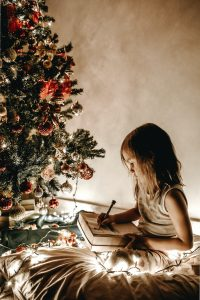 little girl sits next to Christmas tree