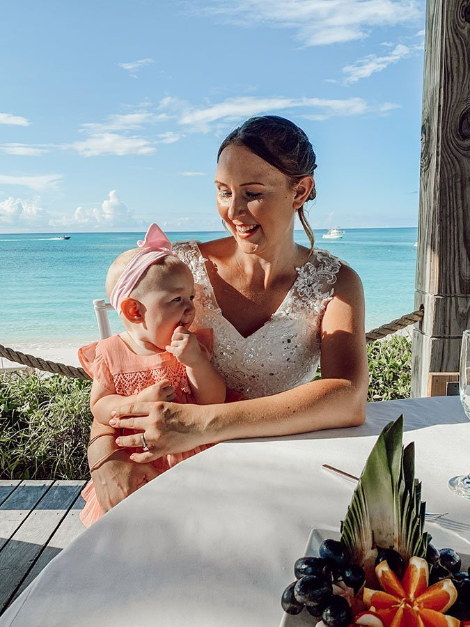 mom in wedding dress smiles down at baby in pink dress sitting on her lap and teething on her fingers