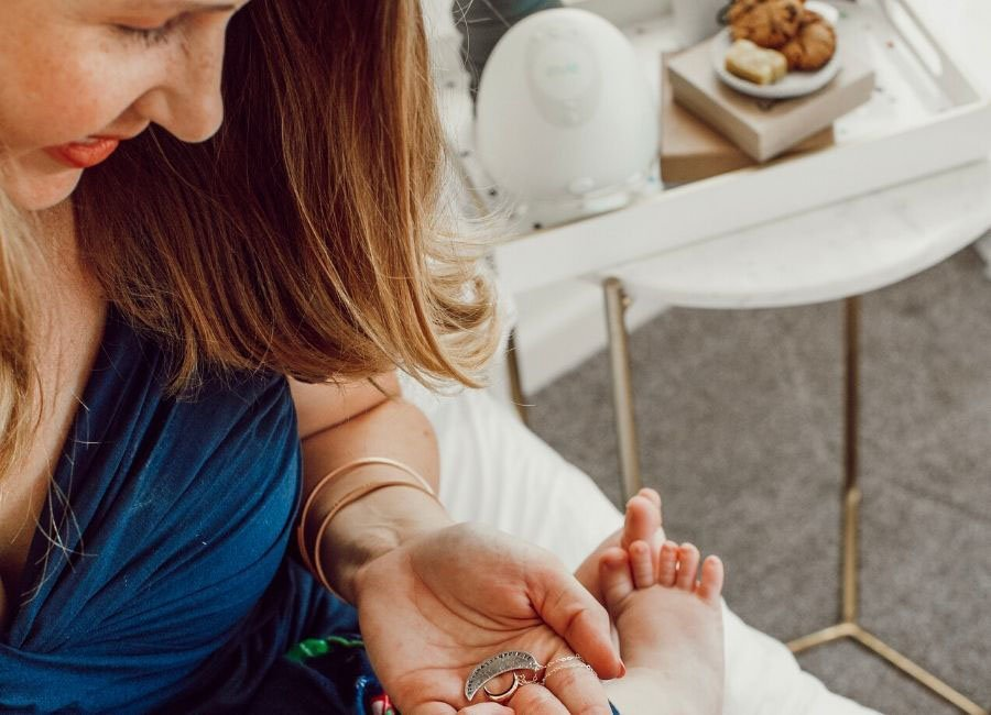 mom looking at necklace while holding baby on her lap