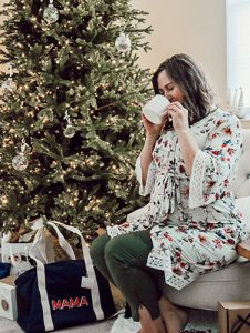 pregnant mom sips drink by Christmas tree