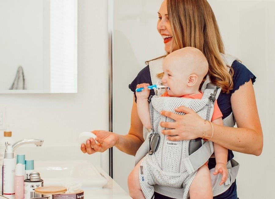 babywearing mom holds lotion stone and smiles at baby in the mirror