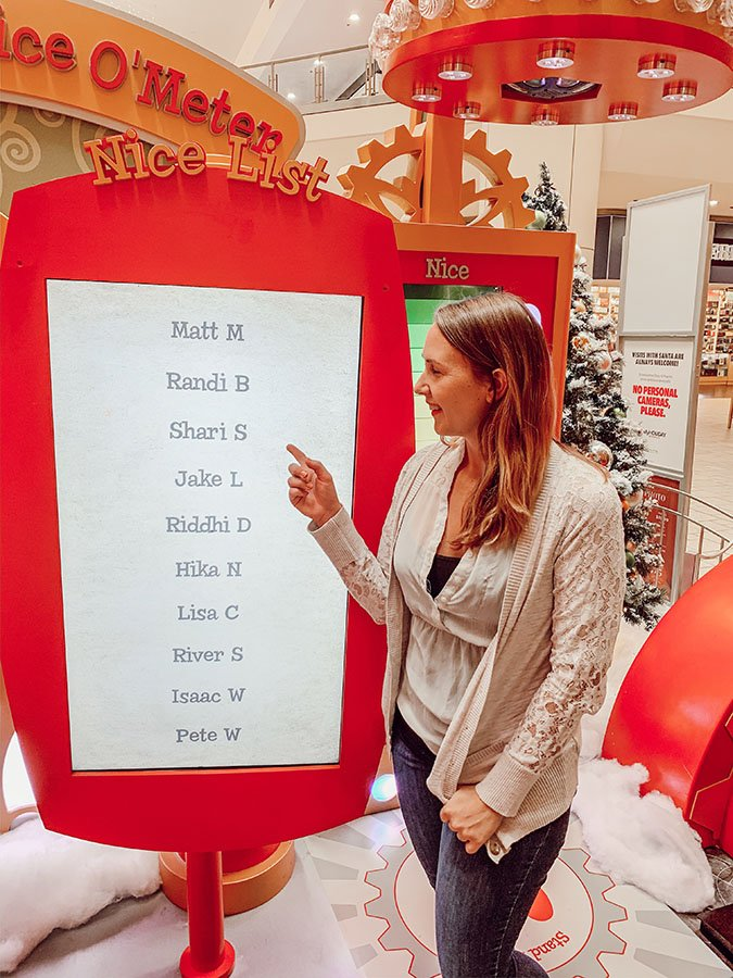 "Woman (Shari) pointing at a monitor called the ""Nice List"" with a list of names on it to show that she's on the list"