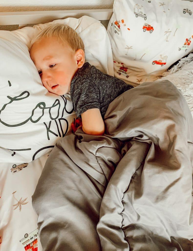 toddler sleeping in his own big kid bed