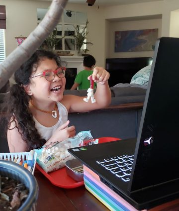 girl with glasses smiles as she holds up her project to friends in camp zoom classroom on her computer
