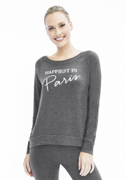 "White woman with blonde hair smiling at camera wearing grey leggings and grey long sleeve shirt that says ""Happiest in Paris"""