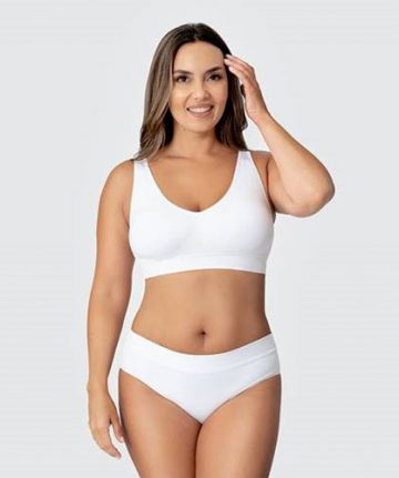 woman stands facing camera with left hand in her hair wearing white shapermint bra and panties