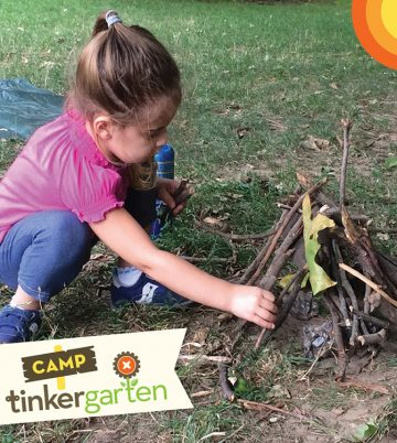 Toddler girl in jeans and pink shirt makes a camp fire with sticks outsie