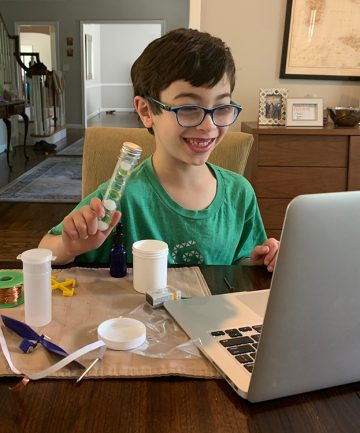 boy smiling at laptop while holding gem project
