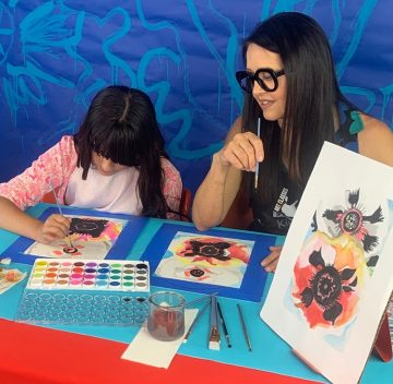 mom looks over at daughter's painting work at art table