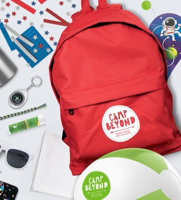 Red backpack an green and white ball with Camp Beyond stickers on them