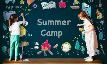 "two girls color on a chalkboard that says ""summer camp"""