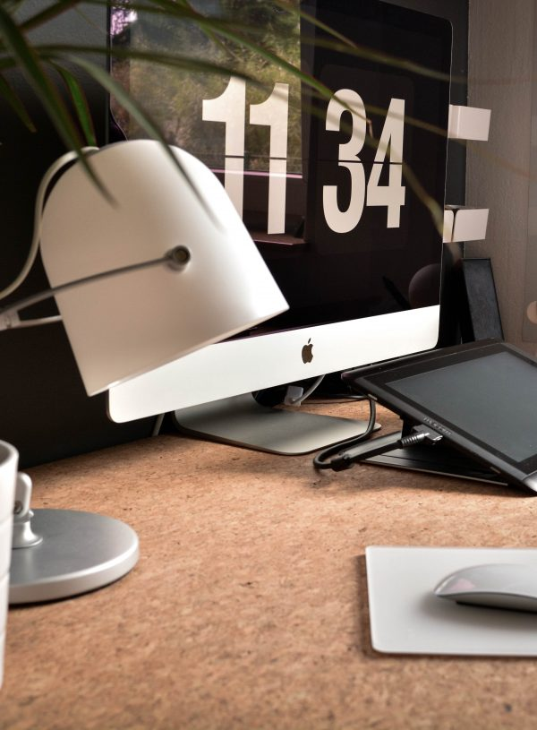 desk with computer, lamp and plant on it with the time 11:34 and a wireless mouse