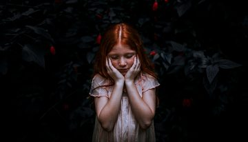 redhaired girl with hands over her cheeks in front of dark background- looks worried