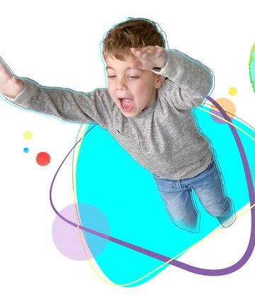 Boy jumping through a white background with colorful shapes