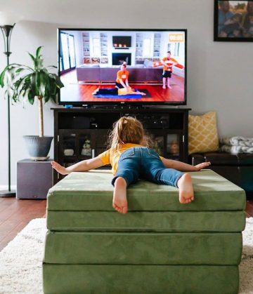girl practices swimming exercises on green nugget sofa while watching YouTube