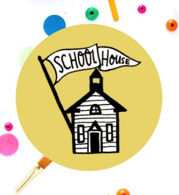 old schoolhouse drawing inside yellow circle with colorful paint dots behind it