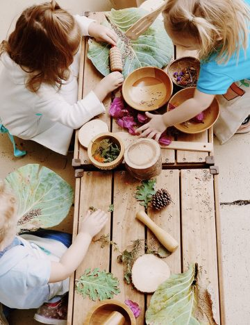 children sit around wooden table with wooden bowls and leaves