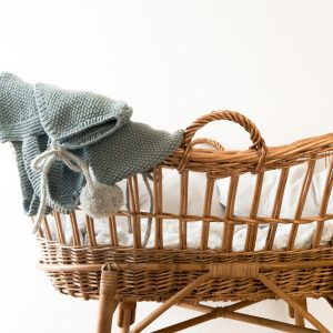wicker bassinet with teal blanket