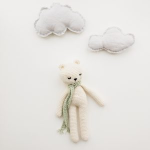 flatlay of stuffed bear wearing scarf with stuffed clouds above