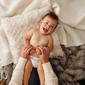 Happy baby laughs during infant massage