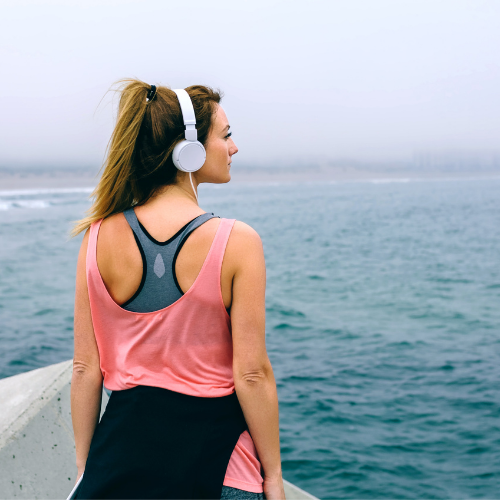 woman in workout clothes looks out at ocean