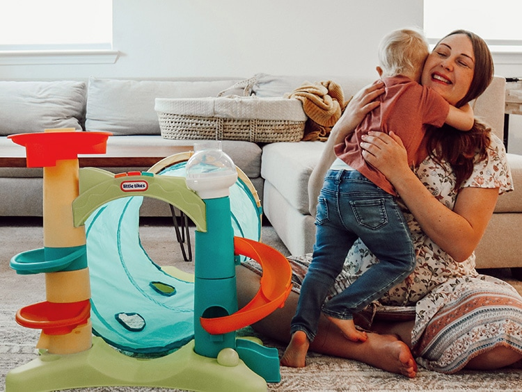 toddler hugs mom next to a play tunnel